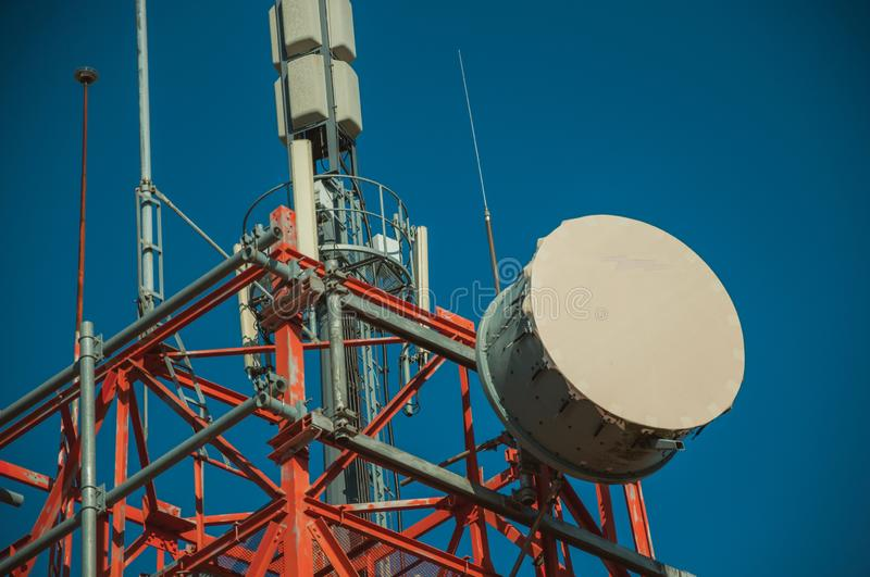 Transmission antenna dish in a tower and blue sky. Transmission antenna dish in a telecommunication cellular network tower and blue sky at Guarda. This friendly royalty free stock photography