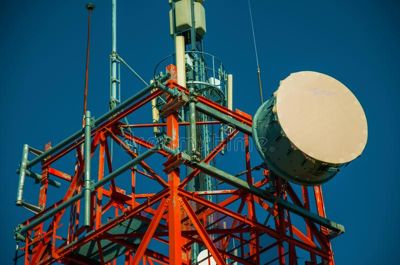 Transmission antenna dish in a tower and blue sky. Transmission antenna dish in a telecommunication cellular network tower and blue sky at Guarda. This friendly stock photo