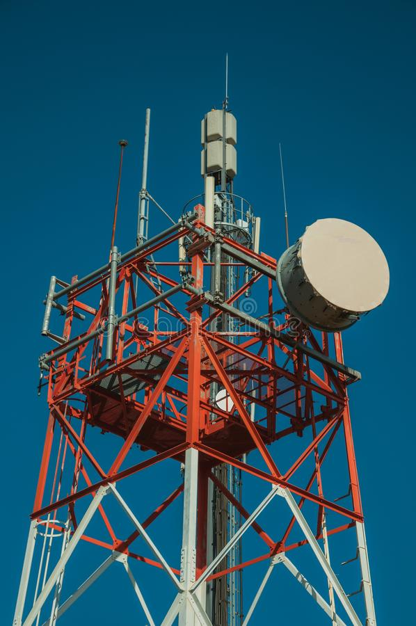 Transmission antenna dish in a tower and blue sky. Transmission antenna dish in a telecommunication cellular network tower and blue sky at Guarda. This friendly stock image
