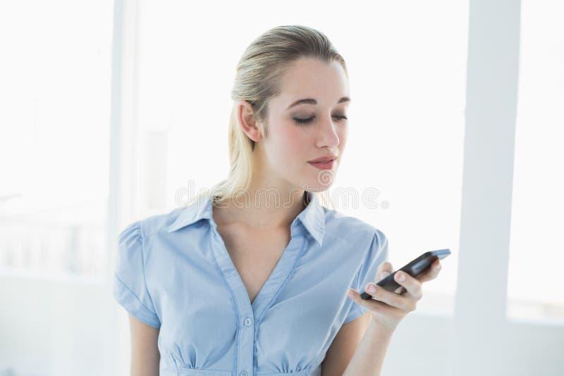 Transmission de messages chique sérieuse de femme d'affaires avec son smartphone image libre de droits