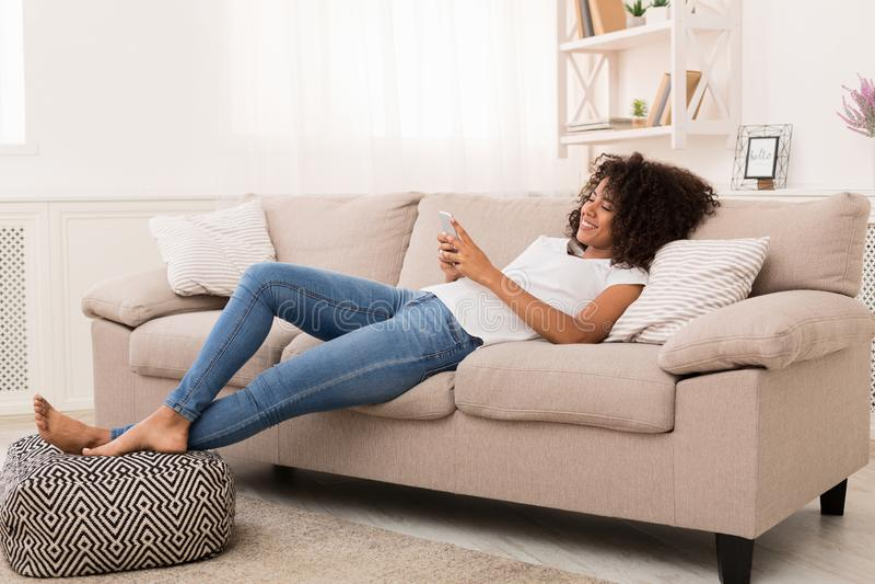 Transmission de messages heureuse de fille d'afro-américain sur le smartphone à la maison photos libres de droits