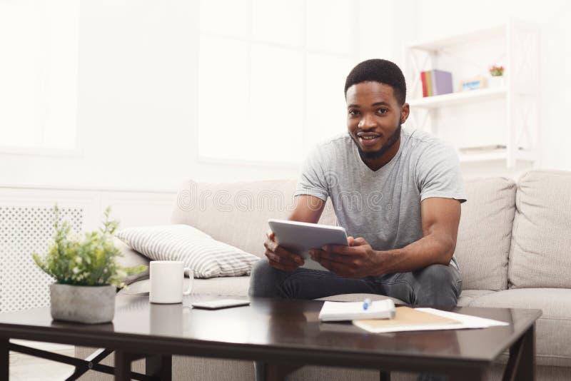 Transmission de messages de jeune homme à la maison en ligne sur le comprimé photographie stock libre de droits