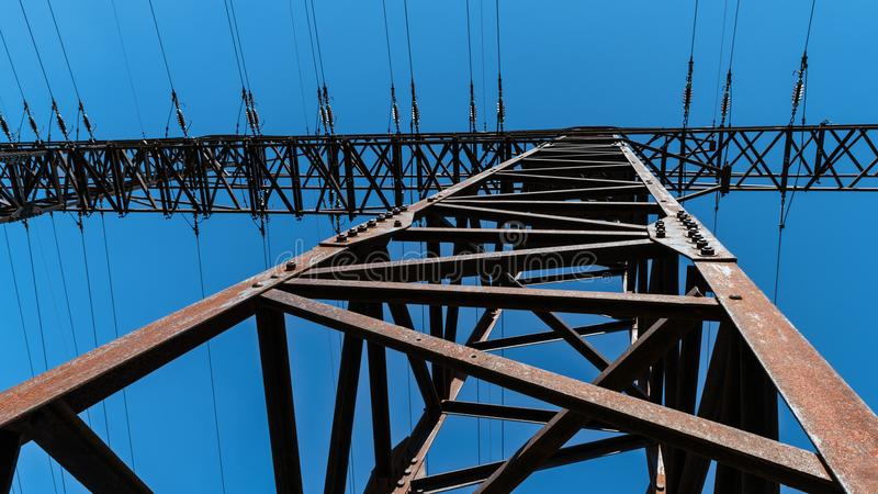 Transmission tower close-up against a blue sky. Silhouette of a tall rusty electricity pylon of power line from a frog`s perspective. Idea of electric energy royalty free stock images