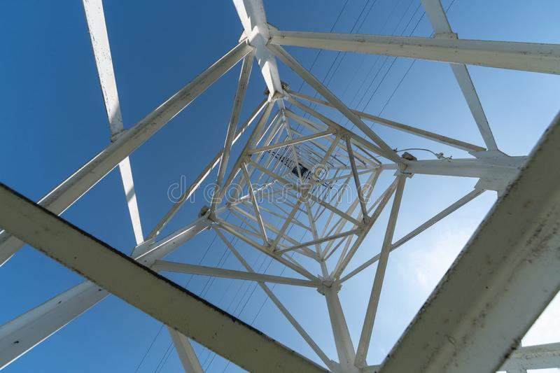Transmission tower, view from below. Overhead pylon power line tower, distribution and transmit electrical energy across large stock photo
