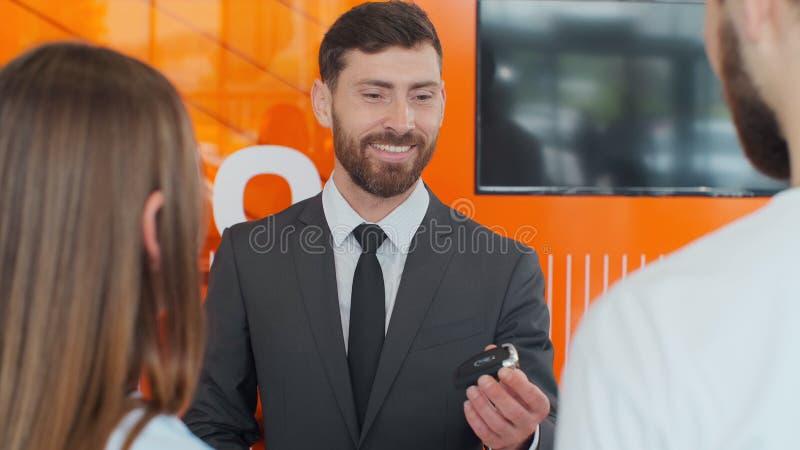 TRANSMIT-Tasten des Verk?ufers zu den jungen Paaren im Auto-Vertragsh?ndler stockfoto