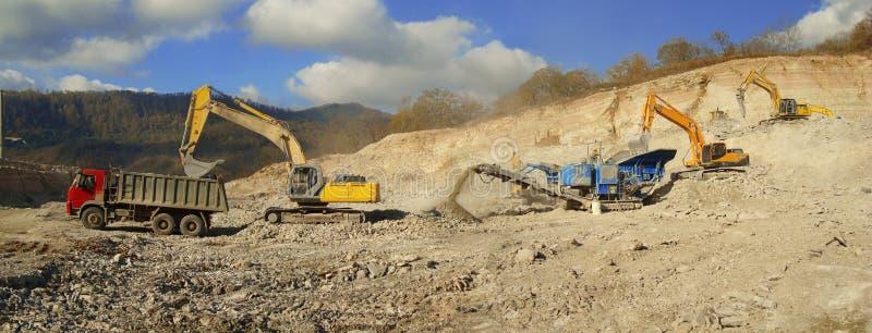Transmitir o processo de esmagamento e de carga da gravilha para a escavadora do caminhão foto de stock royalty free