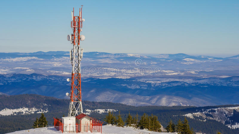 Transmitter tower. Telecommunication tower for GSM network, TV, radio with blue sky and cloud in background stock image
