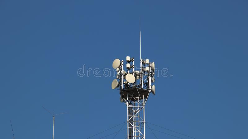 Transmitters of radio signals. electric network. Ecology of power. Technical pole. Iron construction on a blue sky. Strategic reso. Urces. Tutorial of school stock images