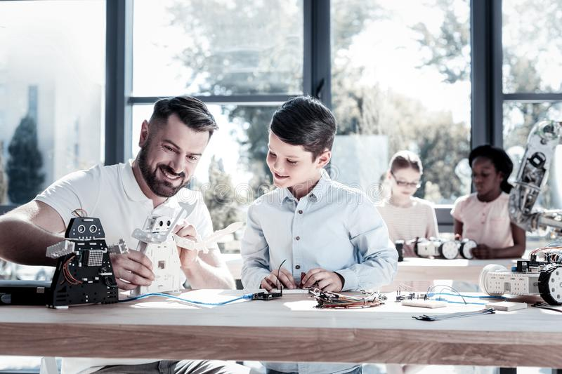 Joyful teacher and student smiling while working on robotic machine. Transmitting knowledge. Cheerful men sitting next to his happy preteen student and smiling stock photography