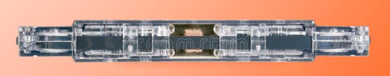 Transparante audiocassette Sluit omhoog mening over de bodem, met oranje gradi?ntachtergrond stock foto