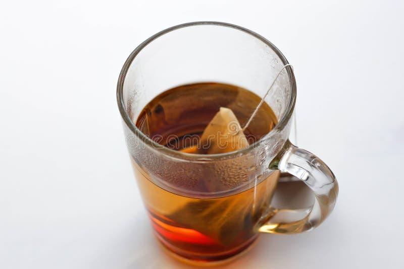 Transparante glasmok en een theezakje Een kop thee Geïsoleerd op wit royalty-vrije stock foto