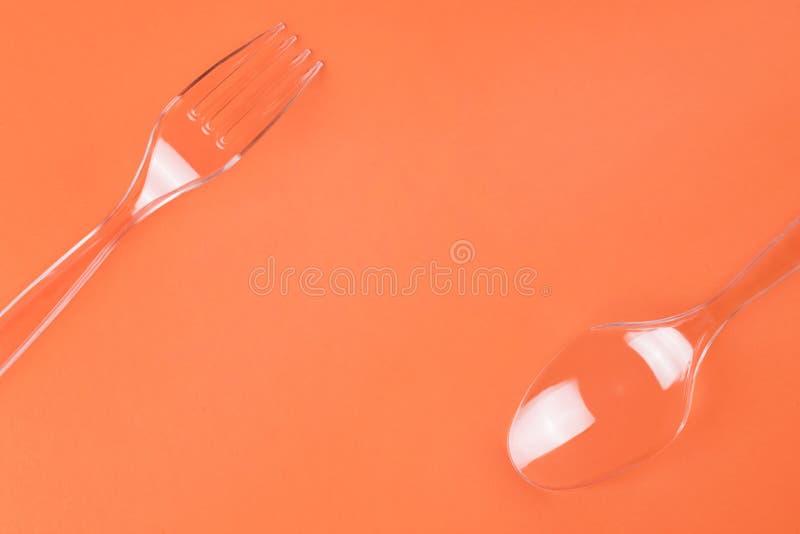 Transparante plastic vork en lepel op oranje achtergrond royalty-vrije stock afbeeldingen