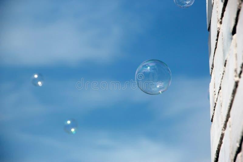 Transparante zeepbel op blauwe hemel met wolken en witte bakstenen muurachtergrond Op een zonnige de zomerdag De textuur van de h stock fotografie