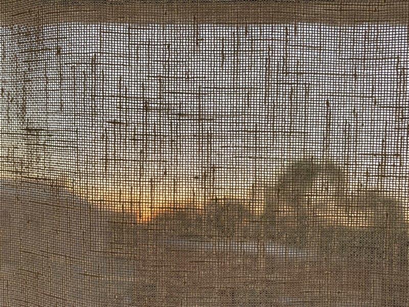 Transparencia del ajuste del sol en una cortina fotografía de archivo