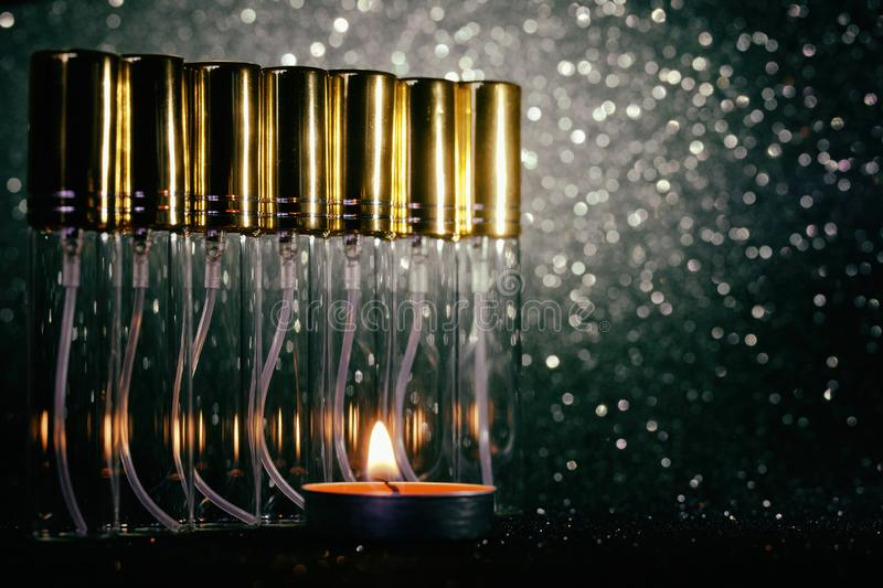 Transparent atomizer sprayers for perfumes on a dark sparkling background. Perfumes and fragrances. Bokeh Vintage processing. Close-up stock photos