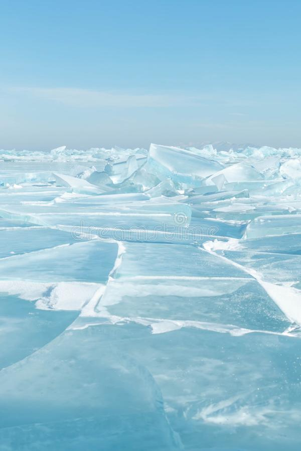Transparent blue cracked ice surface of Lake Baikal in winter stock photography