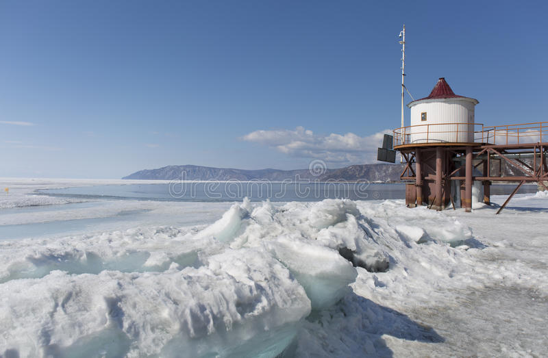Transparent blue ice hummocks on lake Baikal shore. Siberia winter landscape view with lighthouse. Snow-covered ice of. The lake. Big cracks in the ice floe royalty free stock photos