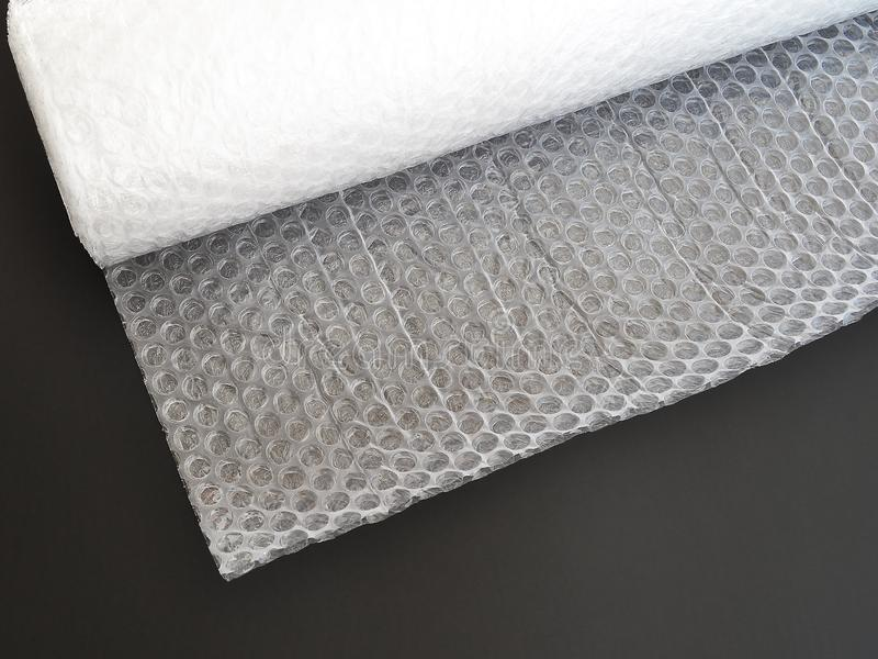 Transparent bubble wrap roll for packaging fragile items on black background top view stock image