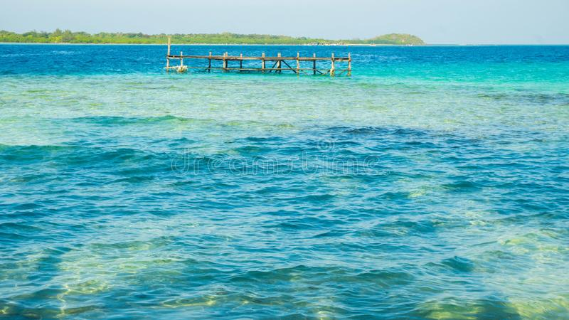 Transparent and clear sea with beautiful landscape background island and boat in distance royalty free stock image