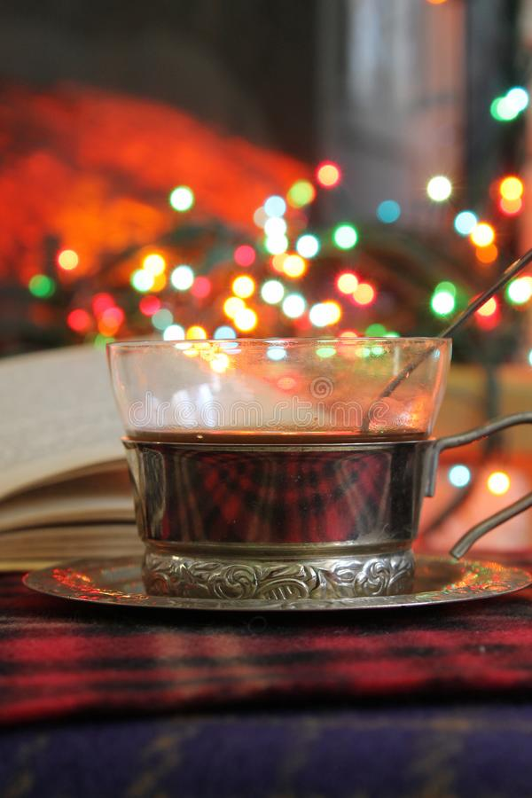 Transparent Cup of tea in a steel Cup holder on the background of a burning fireplace and Christmas garland royalty free stock photo