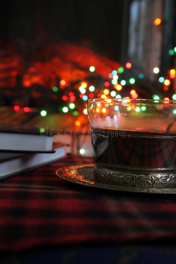 Transparent Cup of tea in a steel Cup holder on the background of a burning fireplace and Christmas garland royalty free stock photography