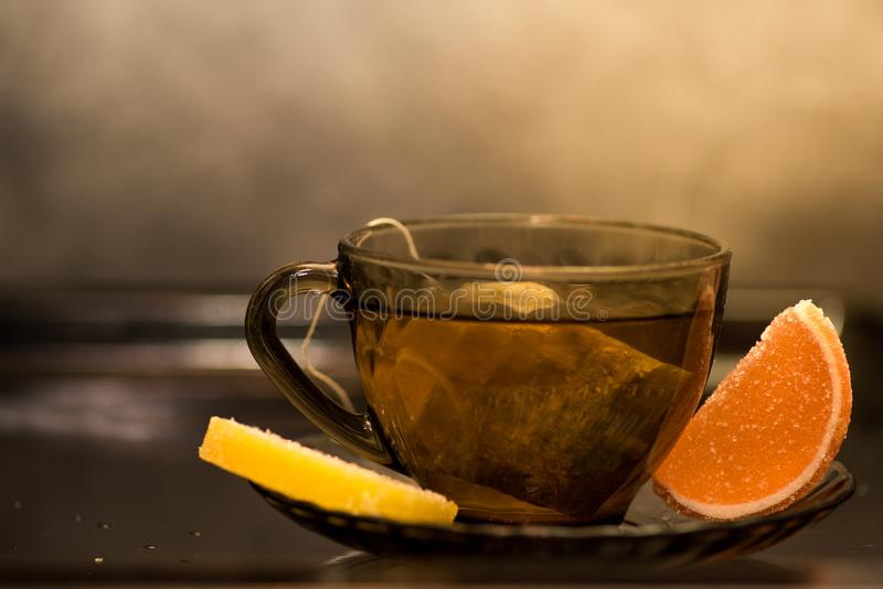 Transparent cup of tea with a lemon and orange marmelade slices stock photos
