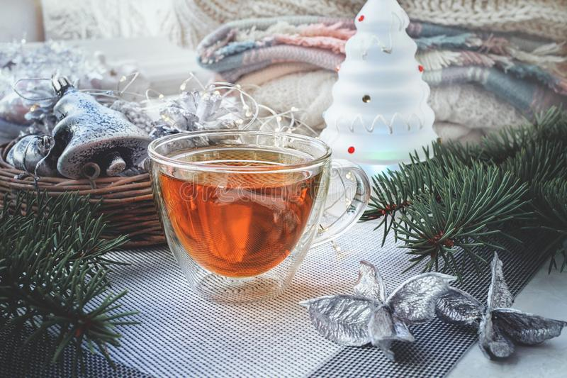 Transparent double bottom glass Cup with hot drink on table with Christmas decor. Warming drink in cold winter stock image