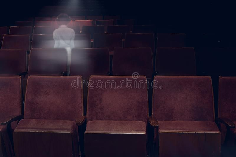 Transparent ghost little girl appears in movie theater. Transparent ghost little girl appears between vintage seat in movie theater, horror film, halloween stock images