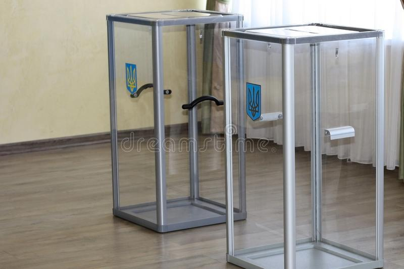 Transparent glass ballot boxes with a coat of arms at the polling station during the elections for the presidency of Ukraine in stock photography