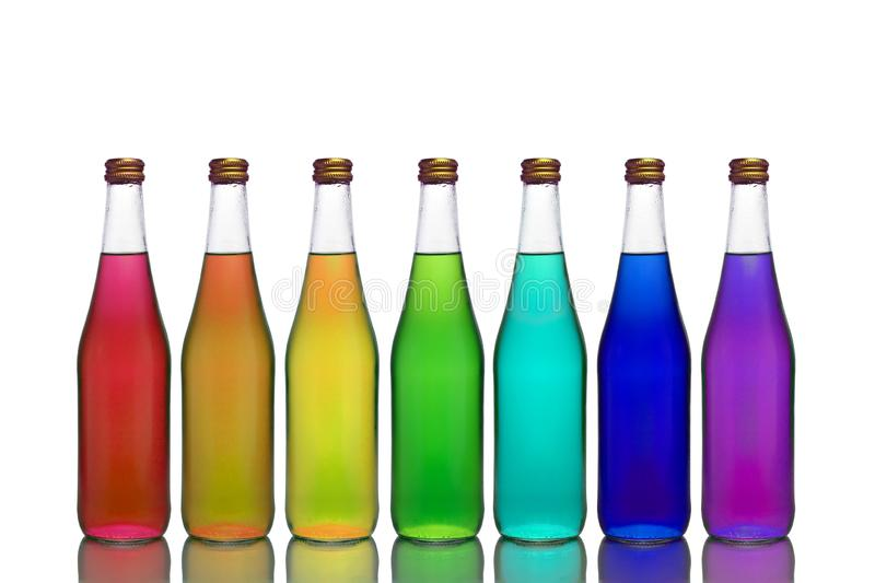 Transparent glass bottles of different colors stand on a mirror surface on a white background stock photo