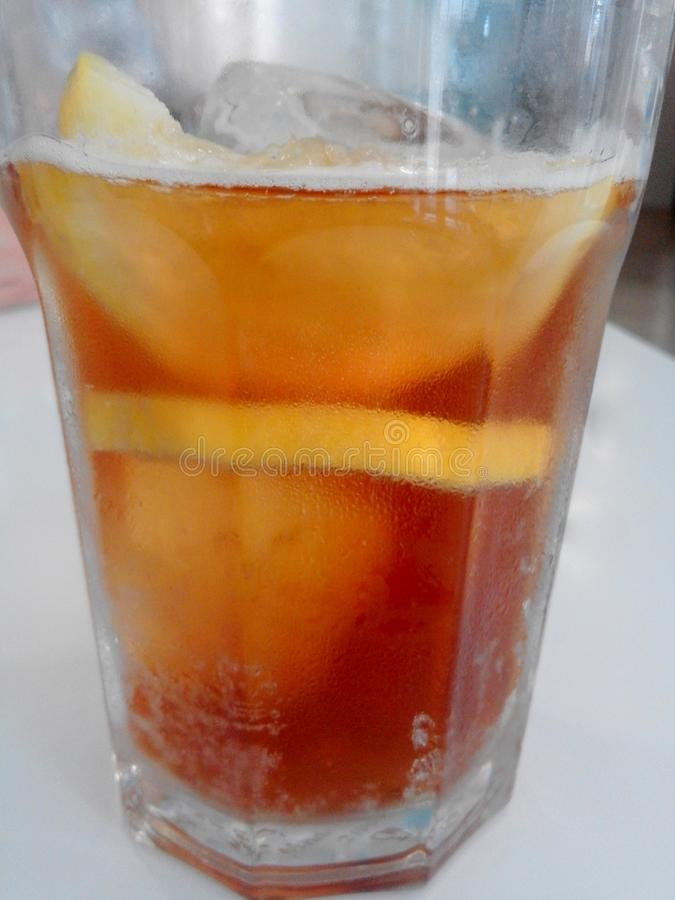 A transparent glass of cold and refresh tea with ice cubes and slice of lemon royalty free stock photos