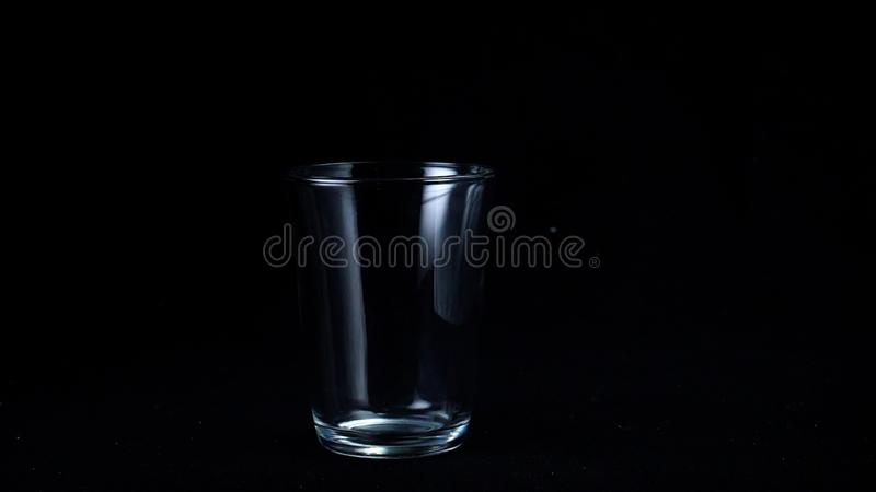 Transparent glass cup on black  background. Frame. Glass for tea stands empty glint from faint white light on stock photos