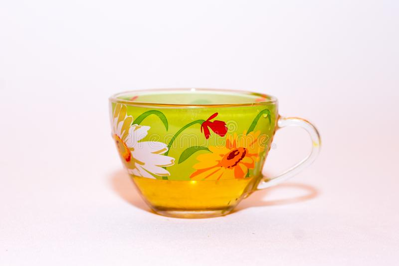 Transparent glass cup with bright colorful pattern and green tea on a white background stock images