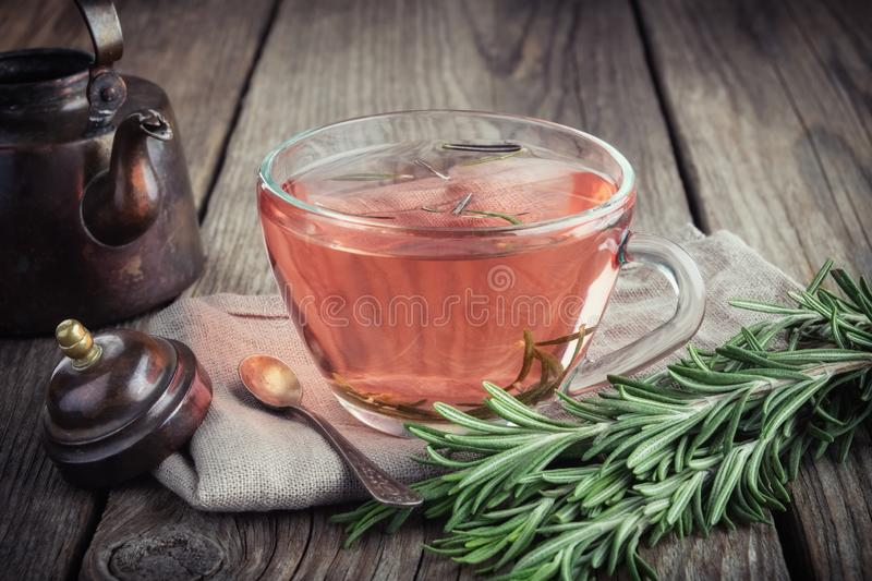 Transparent glass cup of healthy rosemary tea, bunch of fresh rosemary herbs and vintage teapot. royalty free stock photography