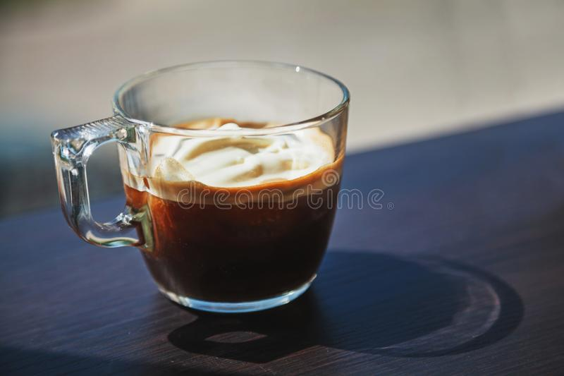 Transparent glass cup of ice coffee with whipped cream placed on royalty free stock photos