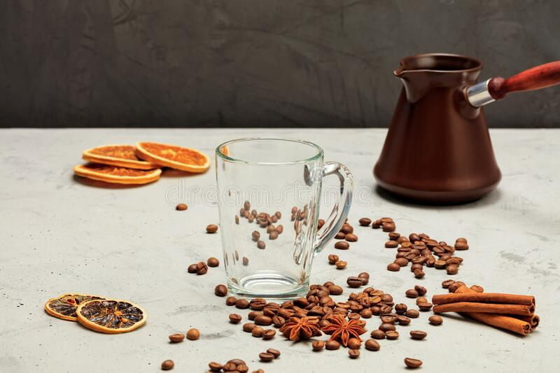 A transparent glass cup stands on a background of gray concrete with coffee beans, dried orange and lemon, anise, cinnamon and royalty free stock photos