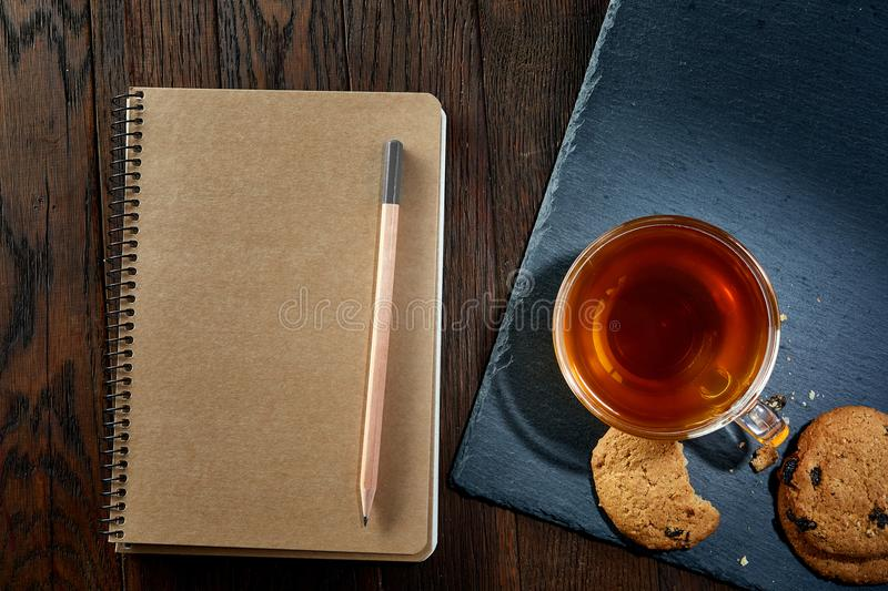 Cup of tea with cookies, workbook and a pencil on a wooden background, top view, vertical. A transparent glass cup of tea with tasty chocolate chips cookies stock photos