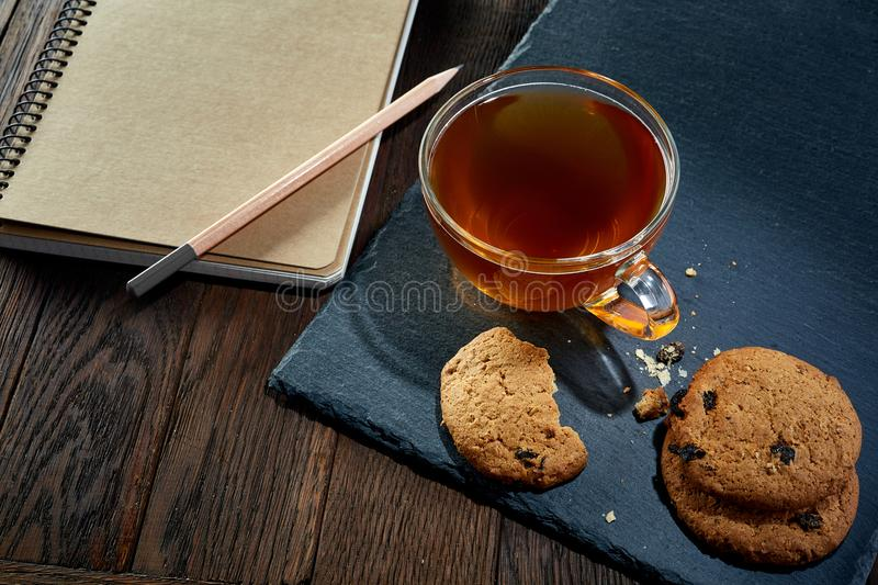 Cup of tea with cookies, workbook and a pencil on a wooden background, top view, vertical. A transparent glass cup of tea with tasty chocolate chips cookies stock image