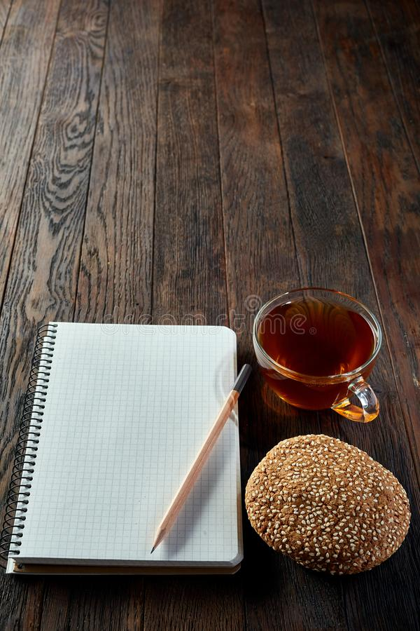 Cup of tea with cookies, workbook and a pencil on a wooden background, top view, vertical. A transparent glass cup of tea with tasty chocolate chips cookies royalty free stock photos