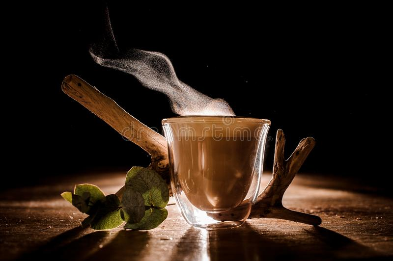 Transparent glass of a delicious hot coffee on the dark background. Beautiful transparent glass of a delicious hot coffee standing on the wooden table with the stock photography