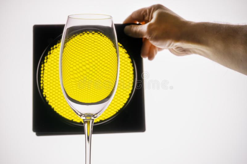 transparent glass holds hand on a background of yellow honeycomb stock photography