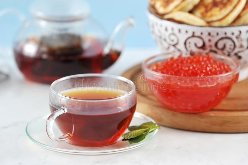 Transparent glass mug with black tea and mint on a background of royalty free stock photo