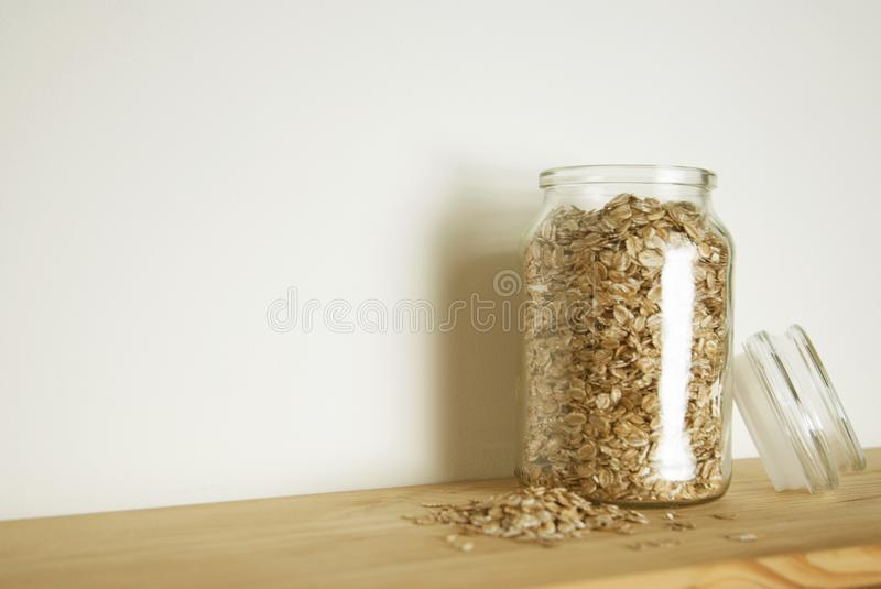 Transparent glass with oat meals in glass jar, isolated isolated on wooden table. Healthy breakfast ingredient. royalty free stock photography