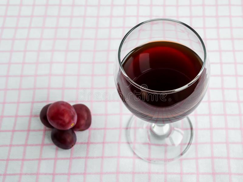 Transparent glass with red wine and few sweet red grapes on white pink checkered tablecloth. Front view royalty free stock image