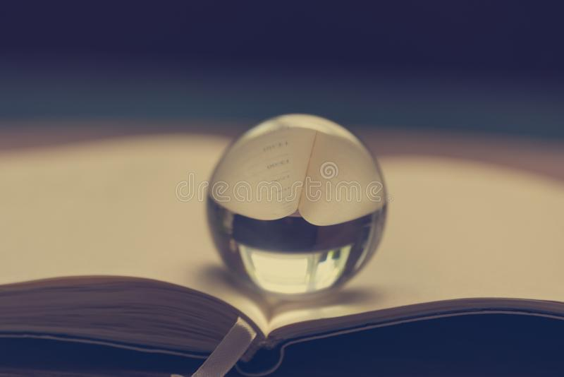 The transparent glass sphere lies on the opened notebook royalty free stock photo