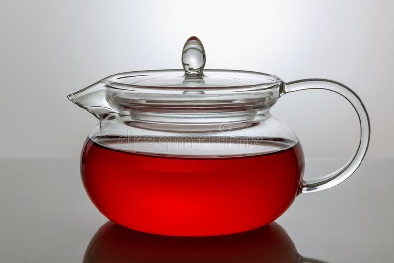 Transparent glass teapot with tea on a gray background stock photo