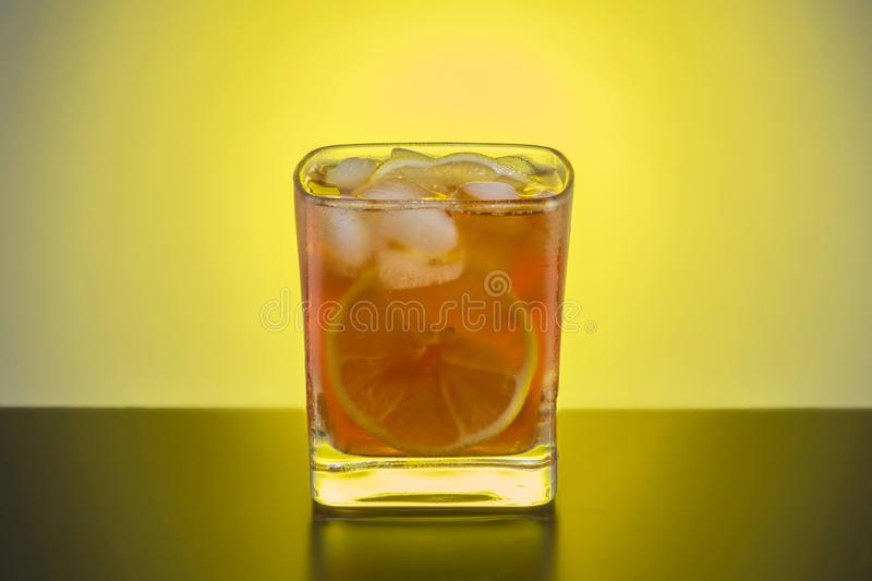 Transparent glass of whiskey with lemon and ice, close-up on the royalty free stock photography