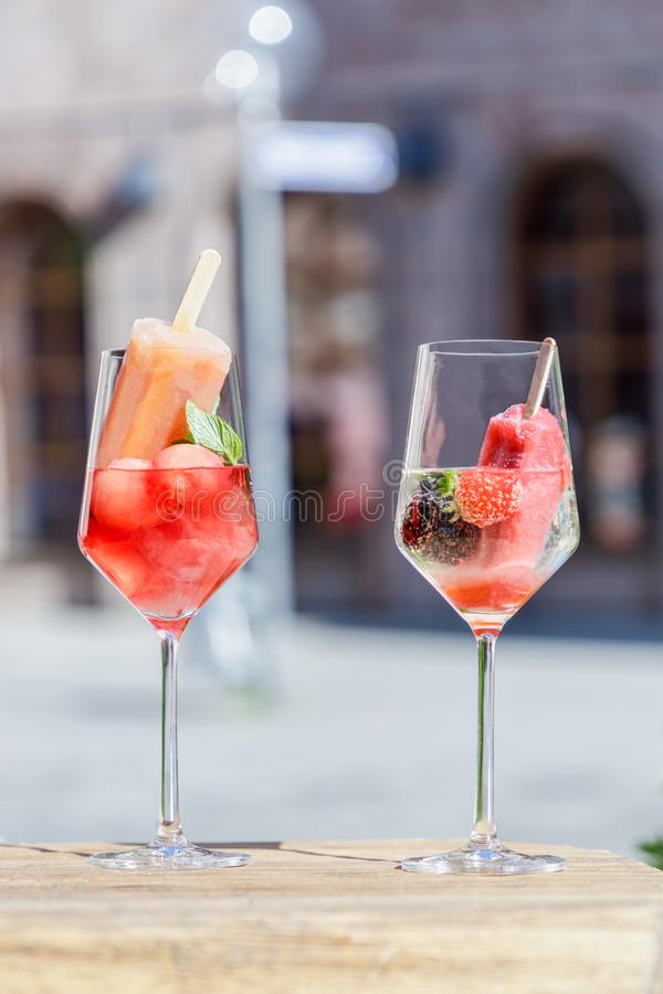 Transparent glasses of wine, popsicles, watermelon, strawberry, blackberry and mint on royalty free stock photos