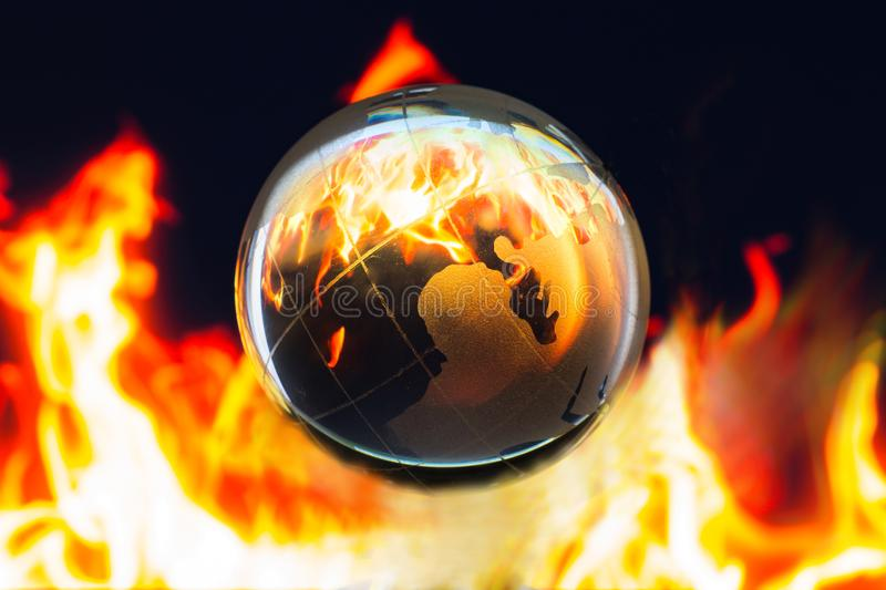 Transparent global on fire inside, Global warming conservative c. Transparent global on fire on dark background, Global warming conservative concept royalty free stock photography