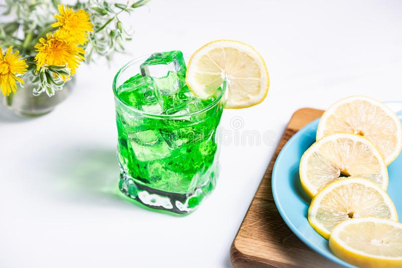 Transparent green drink in a glass with a slice of lemon and ice cubes. Lemon slices on a blue plate stock image